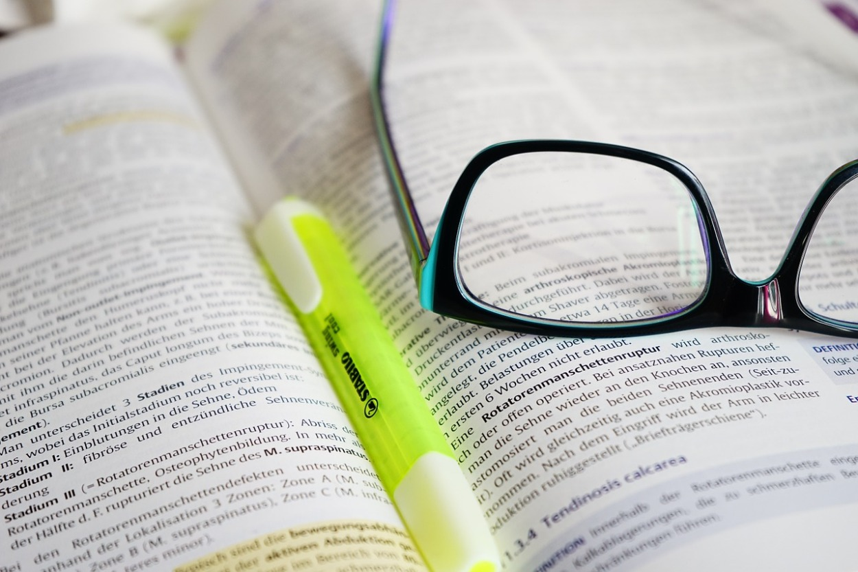 glasses or spectacles with open book